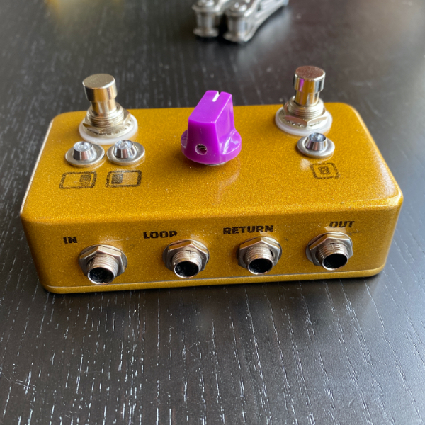 The Haynes Effects positional boost pedal from the back, showing the arrangement of the line input and outputs